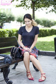 Young woman sits on a bench — Stockfoto