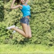 Beautiful girl jumping for joy in a summer park — Stock Photo