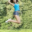 Beautiful girl jumping for joy in a summer park — Stock Photo #34955031