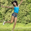 Beautiful girl jumping for joy in a summer park — Stock Photo #34955039