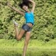 Beautiful girl jumping for joy in a summer park — Stock Photo #34955043