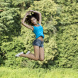 Beautiful girl jumping for joy in a summer park — Stock Photo #34955081