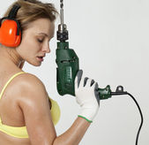 Sexy woman holding a construction drill — Stock Photo