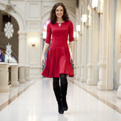 Young beautiful woman in red dress walks in the store — 图库照片