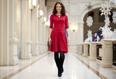 Young beautiful woman in red dress walks in the store — Stock Photo