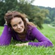Young woman lying on a green lawn — Stock Photo
