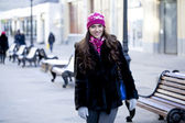Happy young woman on a background of a winter city — Stok fotoğraf