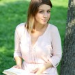 Blonde girl reading a book in the park — Stock Photo #40168519