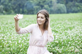 Young woman taking pictures on your phone — Stock Photo