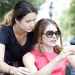 Smiling young girls with cell phone sitting on a bench in a park — Stock Photo #40373811