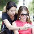 Smiling young girls with cell phone sitting on a bench in a park — Stock Photo