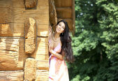 Beautiful woman in bright dress near the wooden wall — Stock Photo