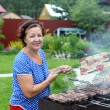 Woman Cooking On A Barbeque in the garden — Stock Photo