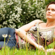 Young woman lying on a green lawn — Stock Photo #42484417