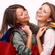 Sisters holding shopping bags on white isolated — Stock Photo