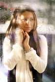 Young woman near the window after the rain — Stock Photo