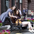 Two girl friends sitting on a bench in the town center — Stock Photo #45799549