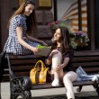 Two girl friends sitting on a bench in the town center — Stock Photo #45799551