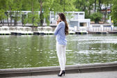 Full length portrait of a beautiful woman in white pants and blu — Stock Photo