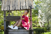 Beautiful girl sits on a wooden pit in the park — Stock Photo