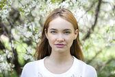 Bella ragazza in piedi vicino a alberi fioriti in primavera gard — Foto Stock