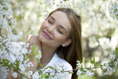 Beautiful young girl standing near blooming trees in spring gard — Stock Photo