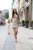 Happy woman in dress on the street — Stock Photo