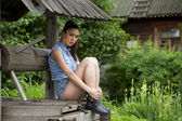 Beautiful young woman sits on a wooden pit in the park  — Stock Photo