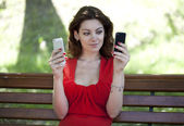 Woman with two smartphones catches Wi fi  — Stock Photo
