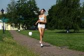 молодая женщина работает в парке летом — Стоковое фото