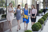 Four beautiful fashion girls walking on the street  — Stok fotoğraf