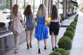 Four beautiful fashion girls walking on the street  — ストック写真