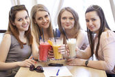 Four young girls have a rest in a summer cafe — Stock Photo