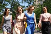 Fyra vackra mode tjejer går på gatan — Stockfoto