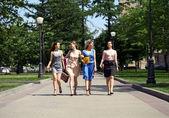 Four beautiful fashion girls walking on the street — Stock Photo