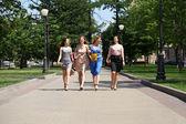 Quattro ragazze moda bella, camminando sulla strada — Foto Stock
