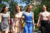 Four beautiful fashion girls walking on the street  — Zdjęcie stockowe