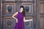 Bella donna in abito luminoso vicino al muro in legno — Foto Stock