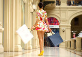 Happy young woman walking in the shop — Stock Photo