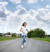 Young woman running along a country road — Stock Photo