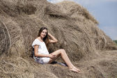 Young beautiful woman in the hayloft in the village — Stock Photo