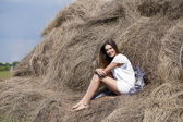 Young beautiful woman in the hayloft in the village — 图库照片