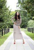 Young woman in sexy long gray dress  — Стоковое фото