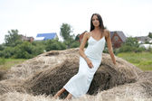 Young beautiful woman in the hayloft in the village — Fotografia Stock