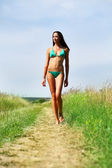 Young slim model in a green bikini walking on rural path — Stock Photo