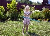 Little girl playing with hula hoop in her garden — Stock Photo