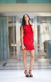 Beautiful woman in red dress in the shop — Stock Photo
