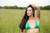 Beautiful model in a green bathing suit standing in the summer f — Stockfoto