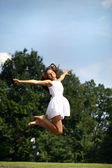Happy young woman jumping in white dress — Stock Photo