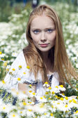 Young woman sitting in a field of chamomile — Stock Photo